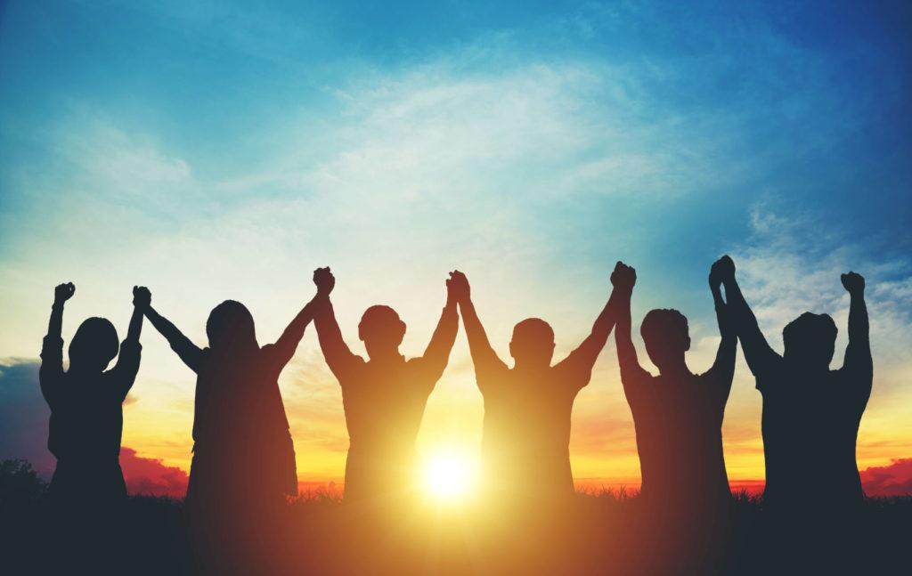 Silhouetten von Menschen, die im Sonnenuntergang ihre Hände in die Luft recken.