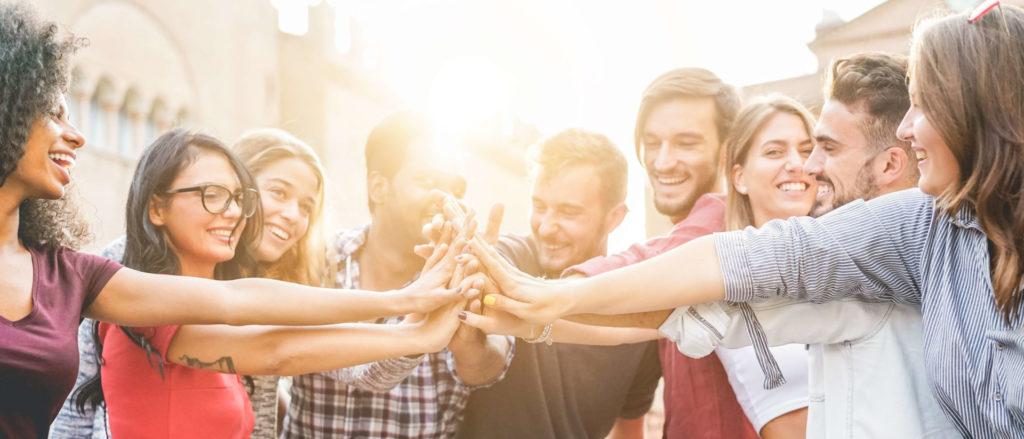 Mehrere junge Menschen halten ihre Hände zusammen – ein Sinnbild für Community Management.