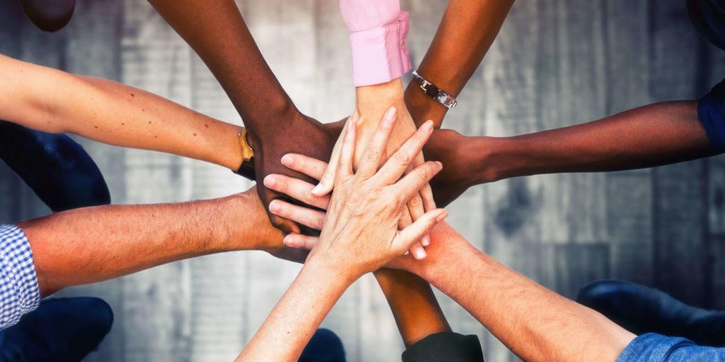 Mehrere Hände liegen übereinander, ein Symbolbild für Community Management.