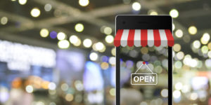 Ein Blick durch ein Smartphone auf einen Shop als Sinnbild für Google my Business, das digitale Schaufenster.