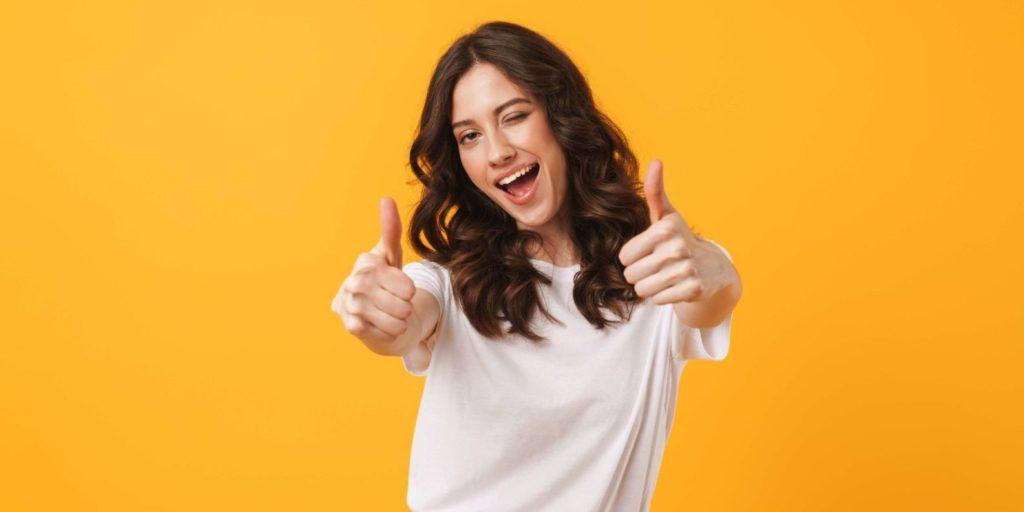 Eine junge Frau hebt Ihre Daumen. Ein Sinnbild dafür, wie Sie begeisterte Newsletter Abonnenten gewinnen.