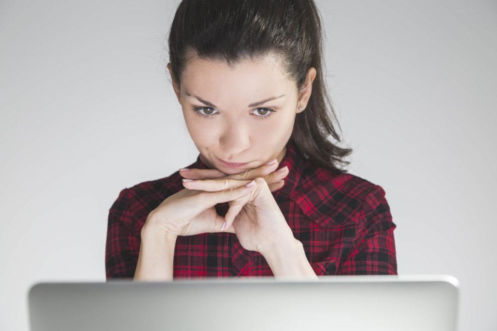 Eine junge Frau wägt am Laptop die Gründe ab, zu den Newsletter Abonnenten dazuzustoßen.