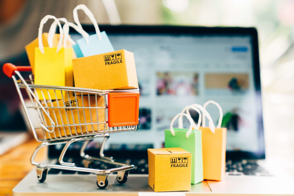 Ein Spielzeugeinkaufswagen steht auf einem Laptop als Symbolbild für einen Online-Marktplatz und Onlineshops.