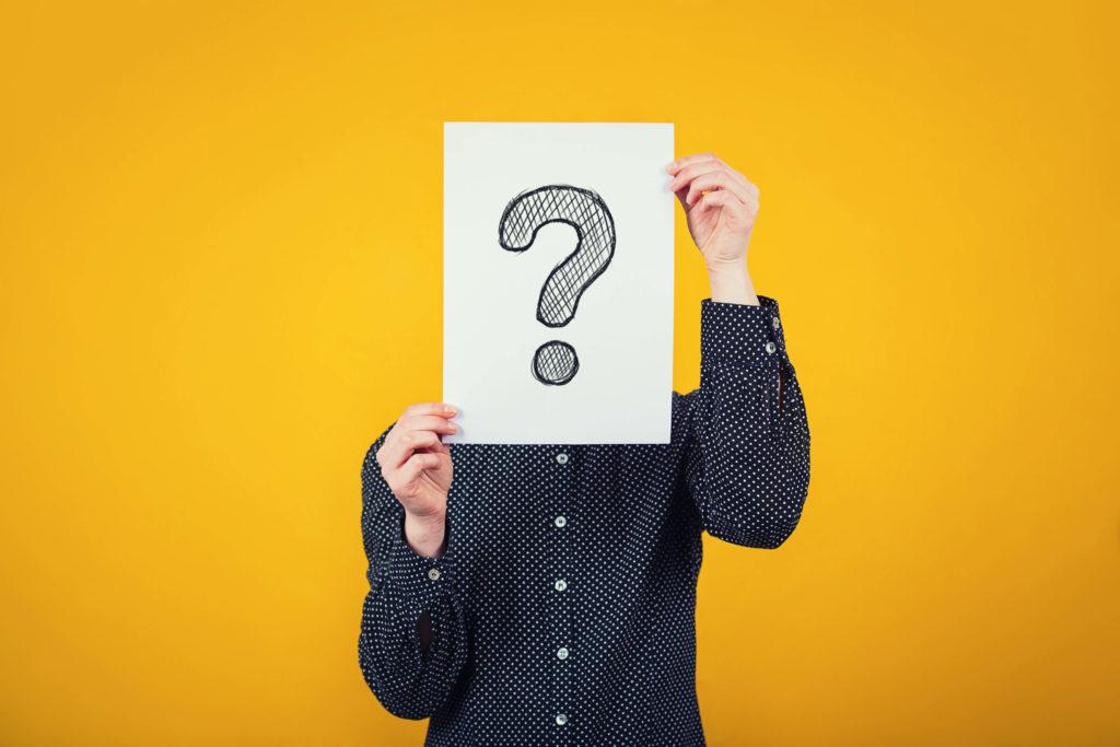 Ein junger Mann hält ein Fragezeichen vor sein Gesicht als Sinnbild für das Unentschieden zwischen Online-Marktplatz und Onlineshop.