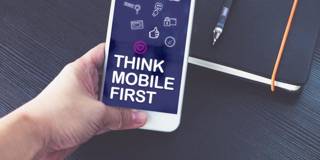 """Eine Hand hält ein Smartphone, auf dem """"Think Mobile First"""" steht"""
