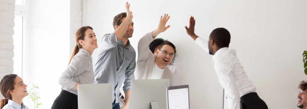 Büromitarbeiter geben sich ein High five. Denn ist die Textwüste erst mal beseitigt, schneidet die Webseite im Ranking vermutlich besser ab.