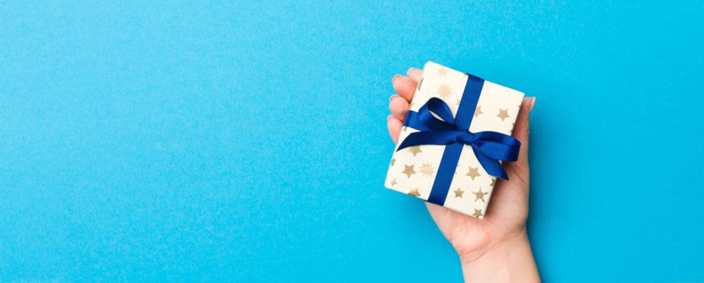 Ein kleines - in weihnachtliches Geschenkpapier eingepacktes - Paket liegt auf einer Handfläche. Symbolbild für ein weihnachtliches Werbegeschenk.