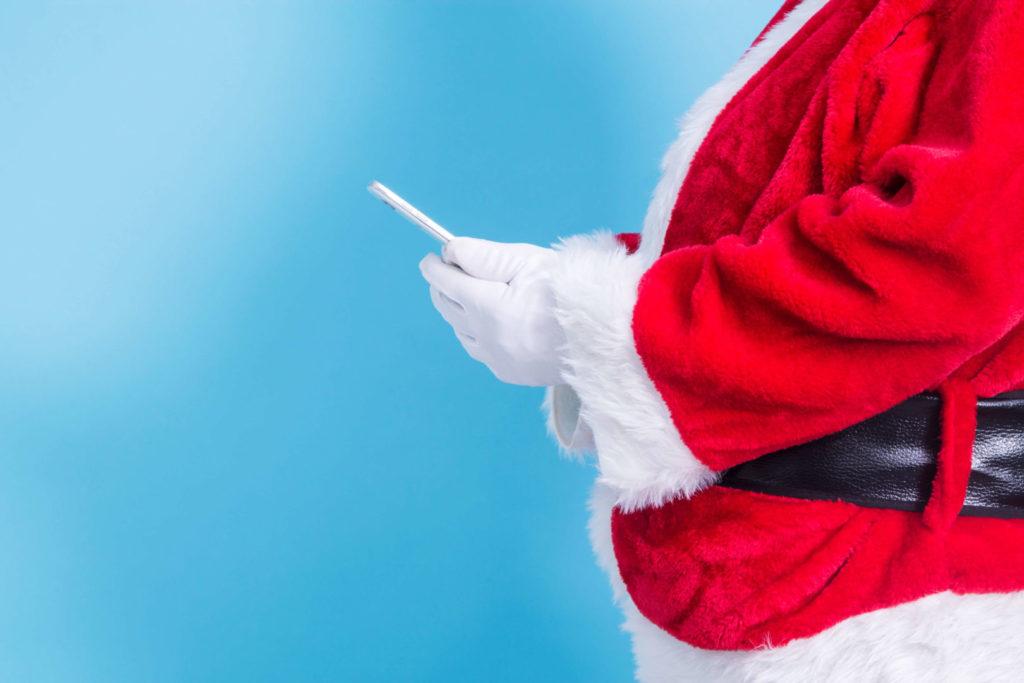 Ein Weihnachtsmann, der ein Smartphone in den Händen hält. Symbolbild für ein digitales Giveaway zum Weihnachtsfest.