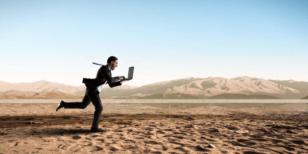 Ein Mann läuft schreiend mit einem aufgeklappten Laptop durch eine Wüstenlandschaft.