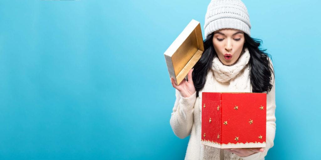 Eine Frau guckt erfreut in eine Geschenkbox, in der sich wohl ein Werbegeschenk befindet.
