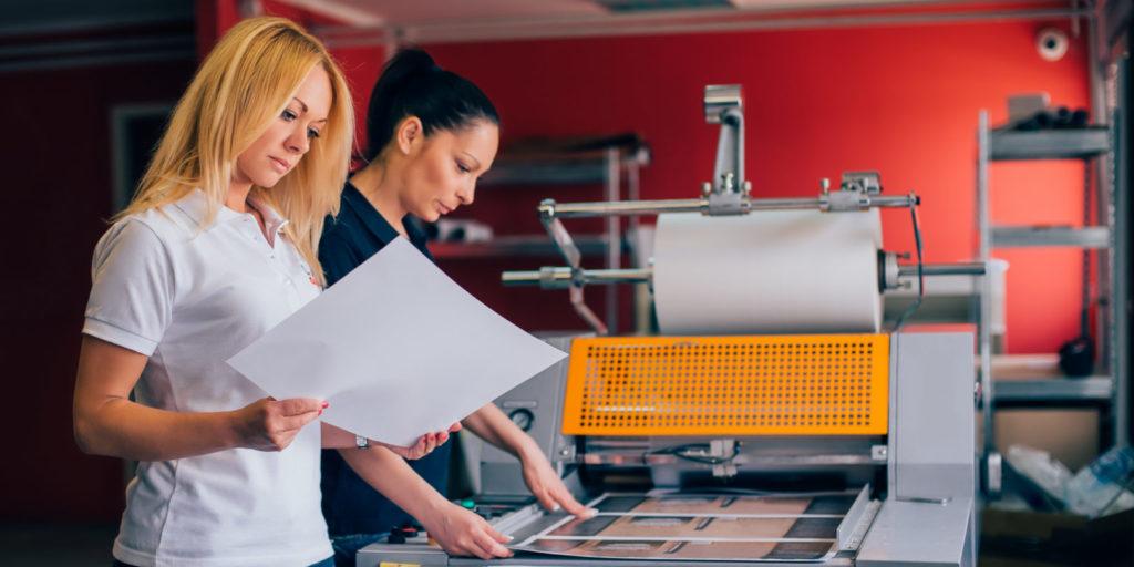 Zwei Mitarbeiterinnen im Print-Marketing prüfen Drucksachen.