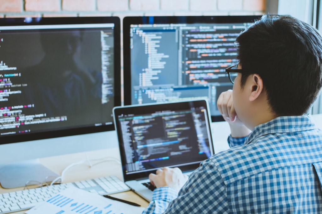 Ein Programmierer prüft seinen Code auf Software Schwachstellen und Sicherheitslücken.