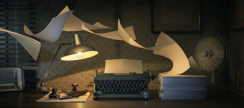 Eine Schreibmaschine auf einem düsteren Tisch, die umweht wird von Papier. Ein Symbolbild für Social-Media-Texte.