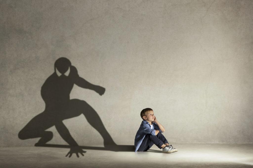 Ein kleiner Junge sitzt vor einer grauen Wand und träumt. Sein Schatten sieht aus wie Spiderman.