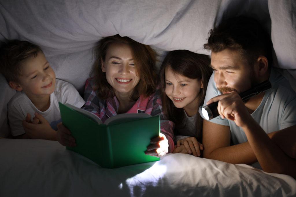 Eltern lesen ihren Kindern eine Gutenachtgeschichte unter der Bettdecke vor.