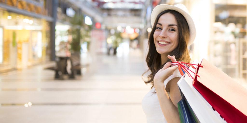 Eine junge Frau shoppt unbeschwert in einer Shoppingmal – ein Sinnbild für freies Shoppen durch mehr Shopware Zahlungsarten.