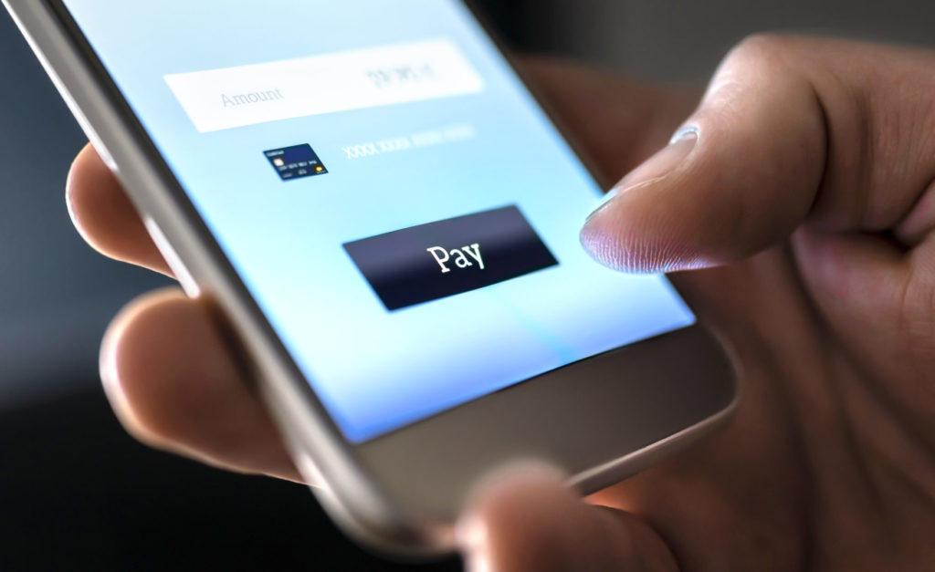 Nahaufnahme einer Hand, die am Smartphone beim Online-Shopping via neuer Shopware Zahlungsarten bezahlt.