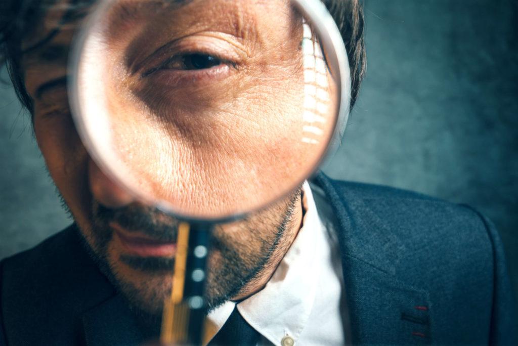 Ein Mann starrt mit einem Auge prüfend durch eine Lupe.