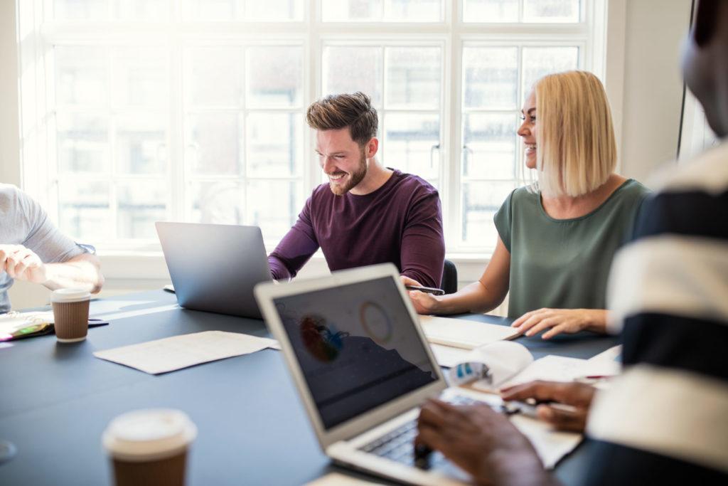 Mitarbeiter von verschiedenen Agentur Arten kooperieren und arbeiten gemeinsam an ihren Laptops.