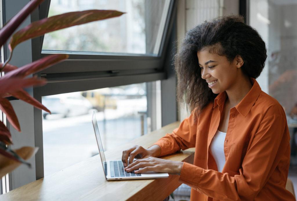 Eine junge Frau nutzt einen Laptop, um in einer Suchmaschine die passenden Ergebnisse zu ihrer Suchintention zu finden.
