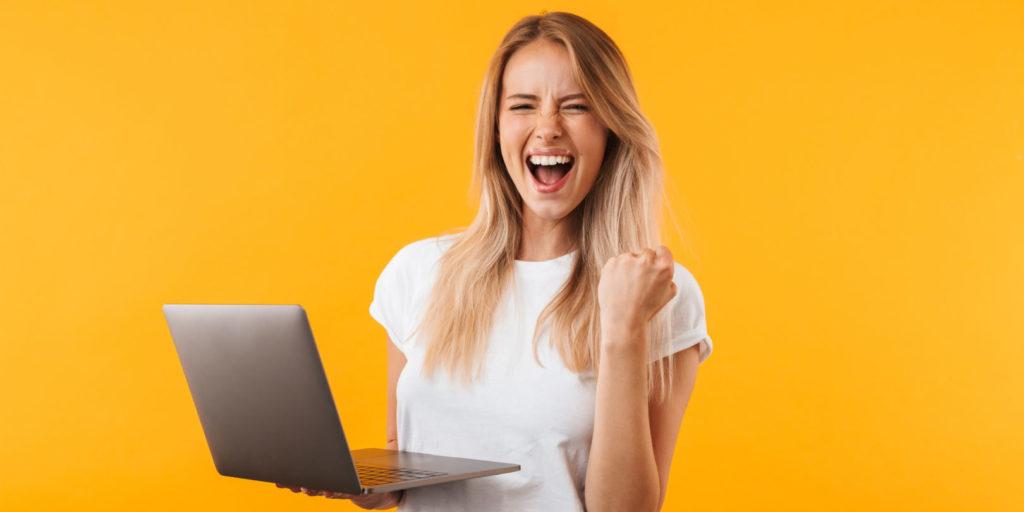 Eine junge Frau mit Laptop in der Hand freut sich über eine erfolgreiche Landingpage.