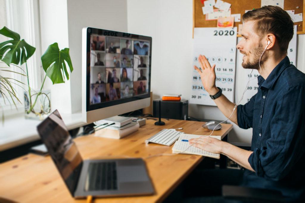 Ein junger Mann nimmt an einem Zoom-Meeting Teil, das via YouTube / Facebook gestreamt wird.