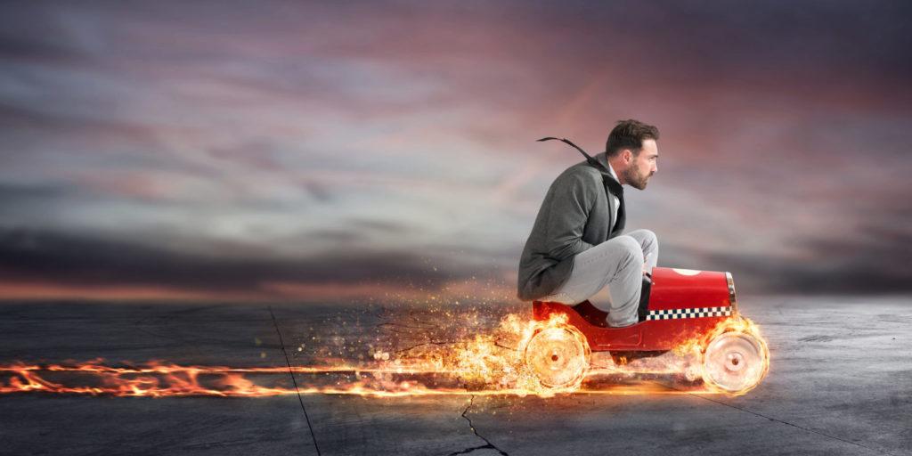 Ein SEO-Manager fährt auf einem brennenden Spielzeugauto – ein Sinnbild für Pagespeed.
