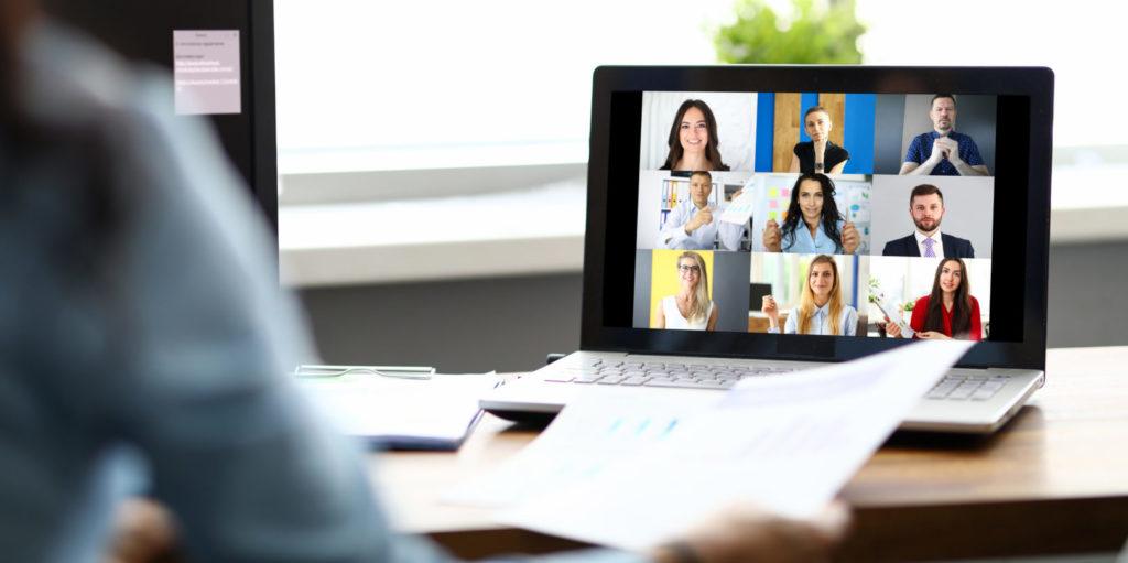 Eine junge Frau schaut ein Zoom-Meeting, das via YouTube und Zoom live gestreamt wird.