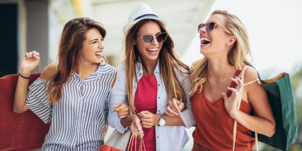Drei junge Frauen shoppen in Geschäften, die sie durch Local SEO gefunden haben.