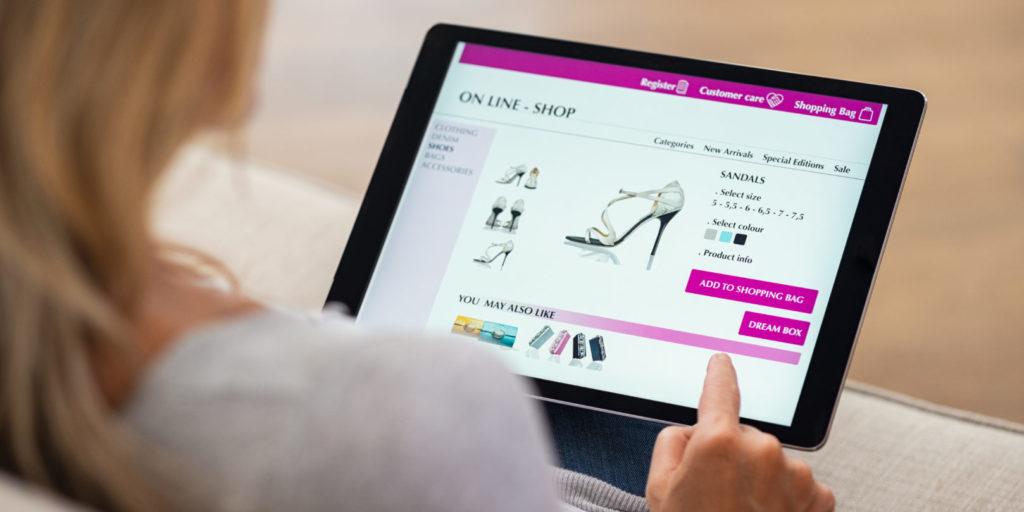 Eine junge Frau kauft an Ihrem Tablet in einem Online-Shop von Shopware ein.