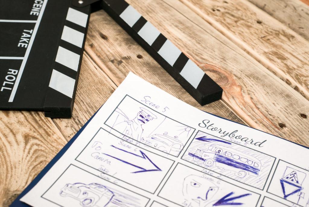 Das Storyboard für einen Imagefilm liegt auf einem Tisch neben einer Filmklappe.