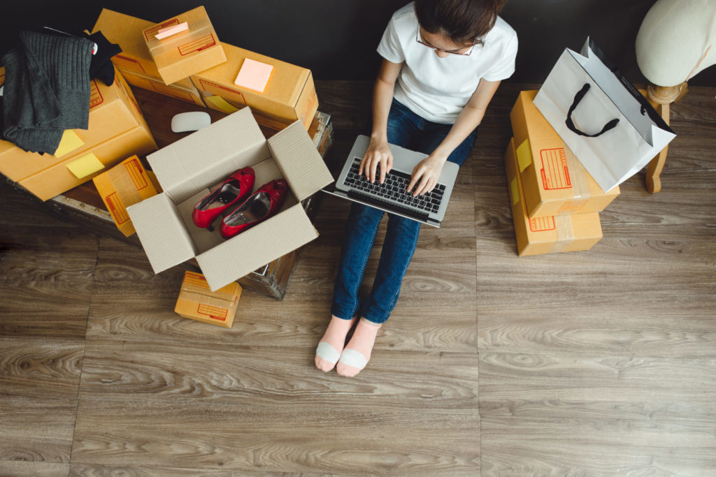 Eine junge Frau sitzt mit Laptop zwischen Einkaufsboxen, die sie über einen Online-Shop auf Shopware Basis bestellt hat.