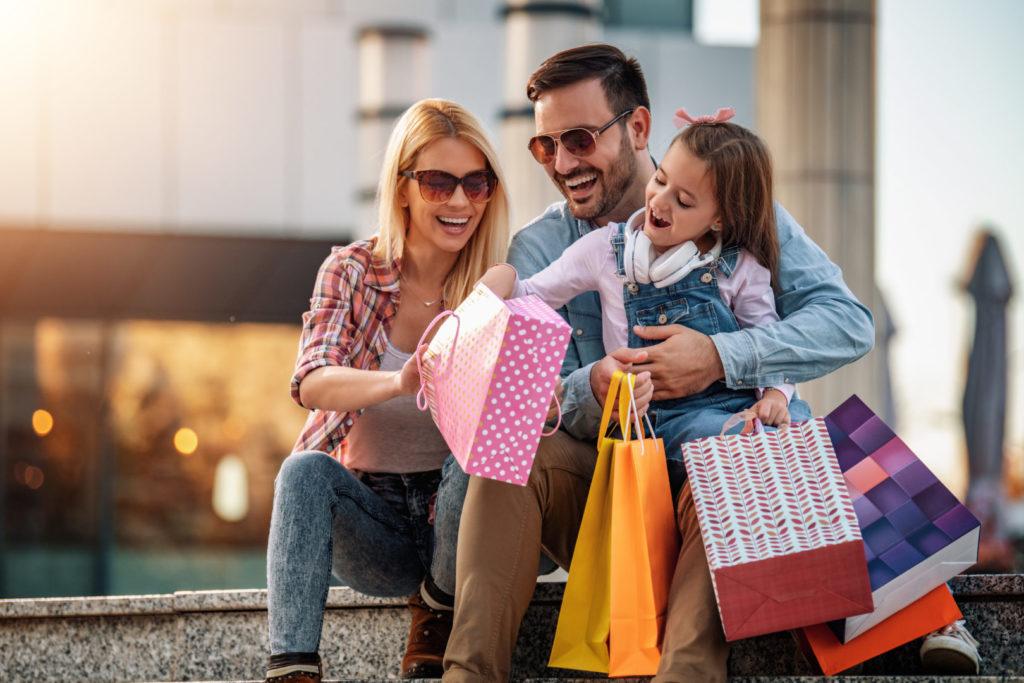 Eine glückliche Familie sitzt mit Shopping-Tüten auf einer Treppe.