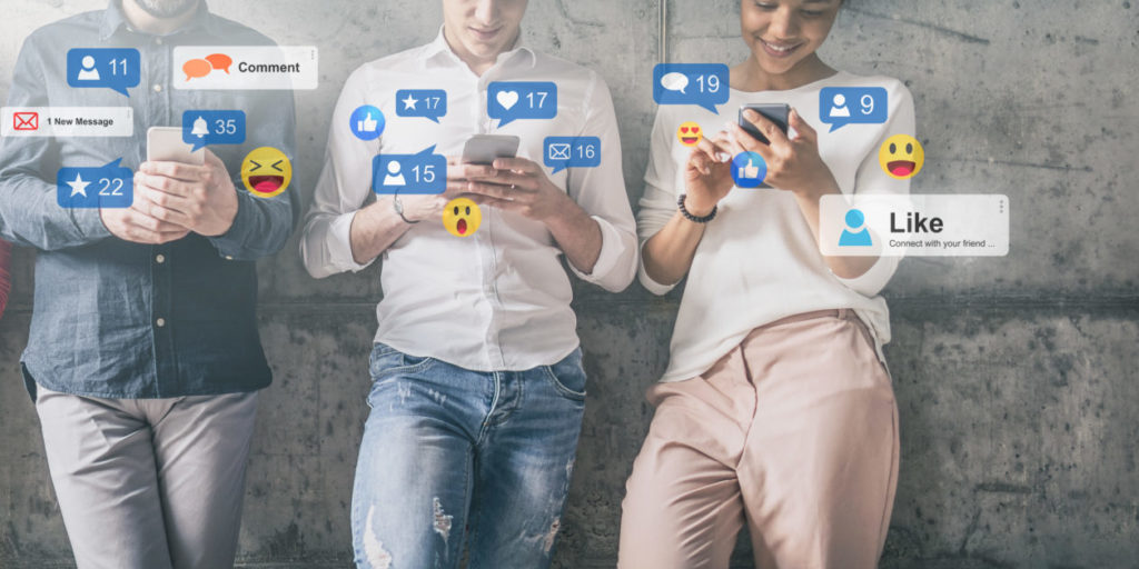 Junge Menschen lehnen an einer Wand und lesen einen Social-Media-Vergleich auf ihren Smartphones.