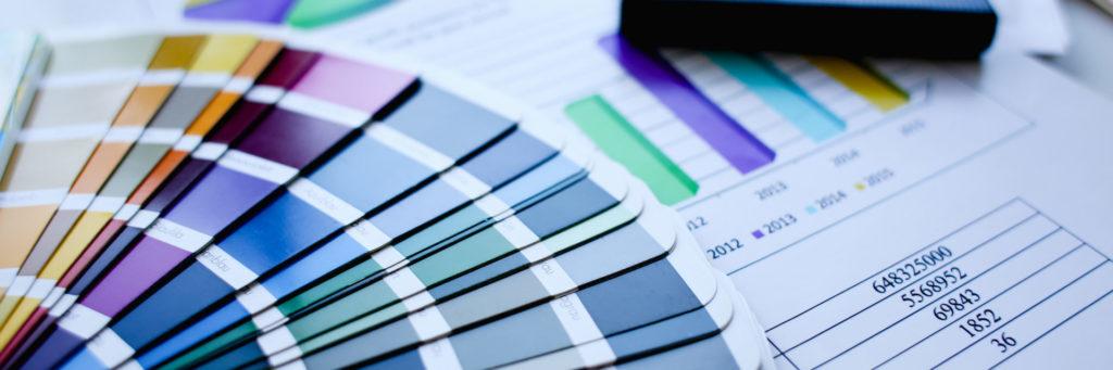 Farbvorlagen für eine Printwerbung liegen auf einem Tisch.