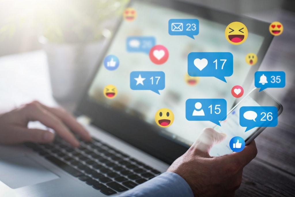 Ein Online-Marketer eines Unternehmens aus dem Mittelstand liest am Laptop einen Social-Media-Vergleich.