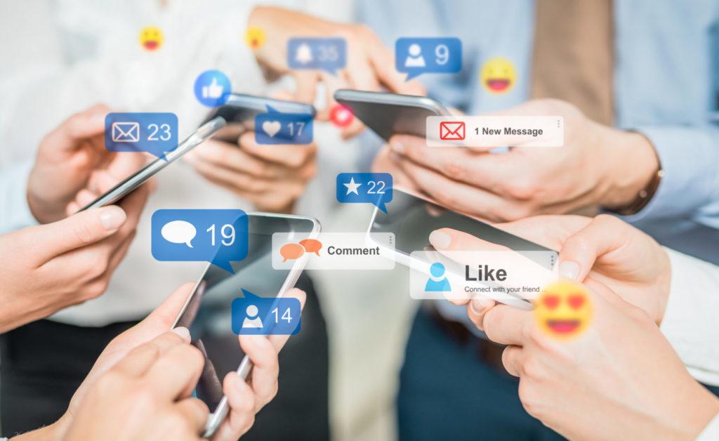 Junge Menschen halten ihre Smartphones zusammen und vergleichen ihre Social-Media-Profile.