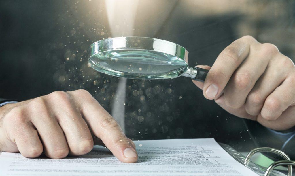Ein Online-Marketing-Mitarbeiter prüft mit Lupe Statistiken zu Keywords und Suchvolumen.