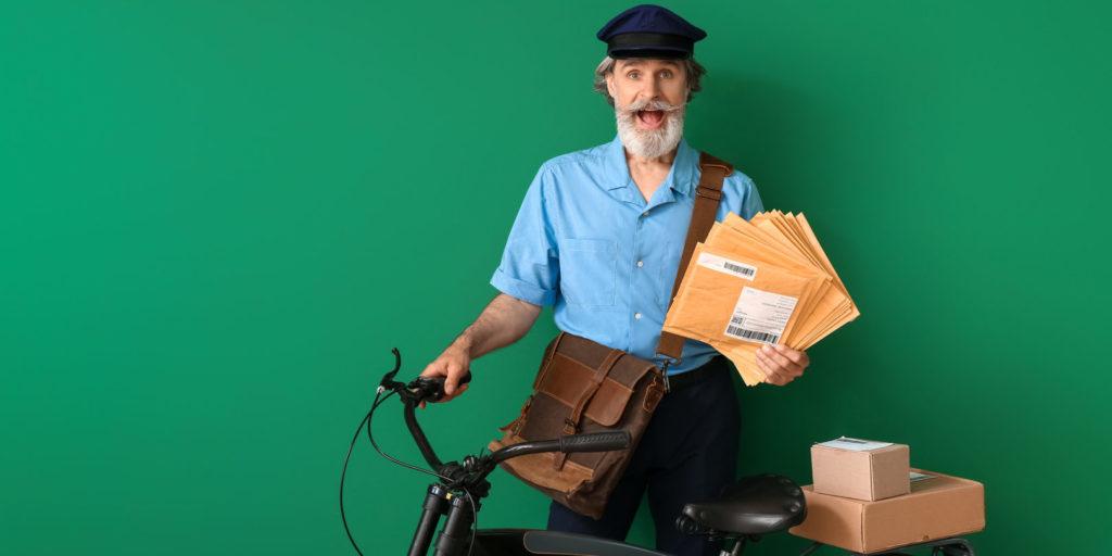 Ein alter Briefträger posiert mit Fahrrad als Symbolbild für erfolgreiche E-Mail-Newsletter.