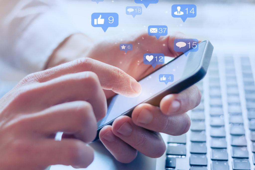 Ein Online-Marketer erstellt am Smartphone Social-Media-Content.